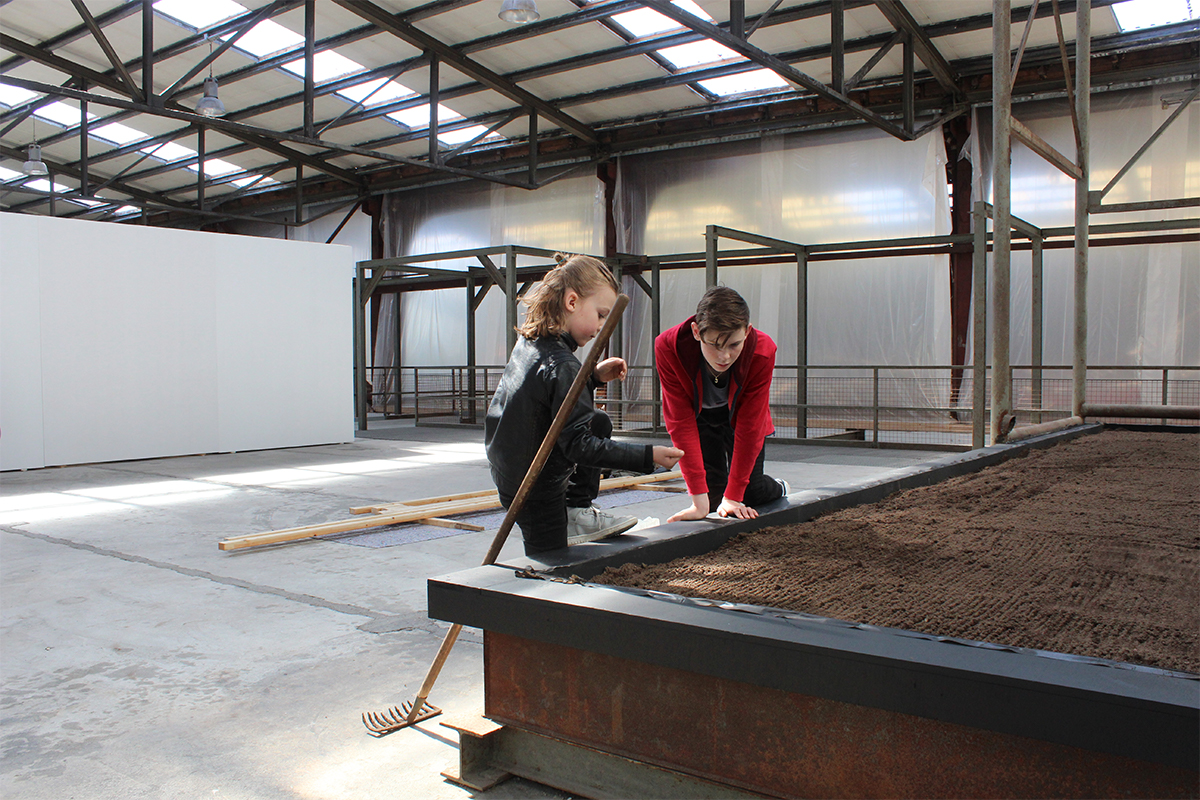 Marie Markman, Assistants sowing a piece of landscape in exhibition hall, 2017, NordArt. Photo by Marie Markman. Courtesy of the artist.