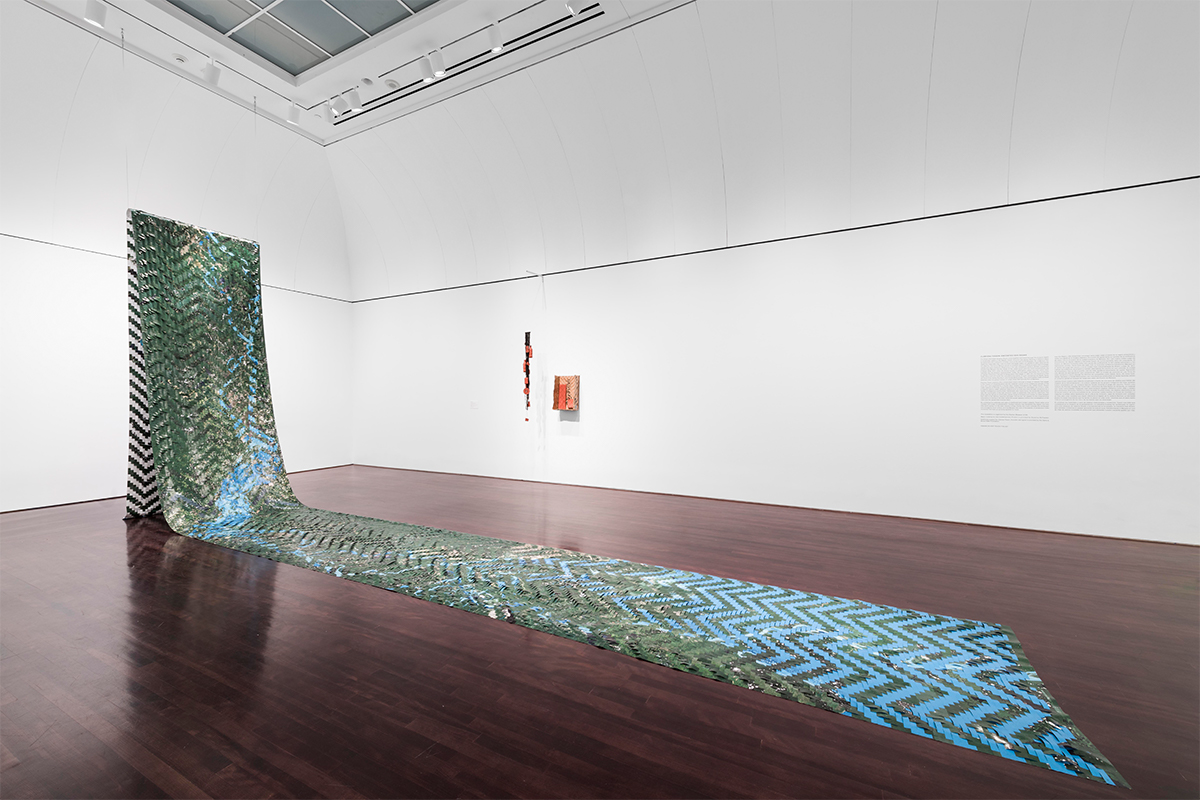 Clarissa Tossin, Encontro das Águas (Meeting of Waters), 2016-18. 4 1/2 ft x 50 ft, Woven archival inkjet print on vinyl, terra-cotta objects, fishnet, thread, and woven indigenous baskets and backpack made out of Amazon.com boxes, Installation view at Blanton Museum of Art, New York.