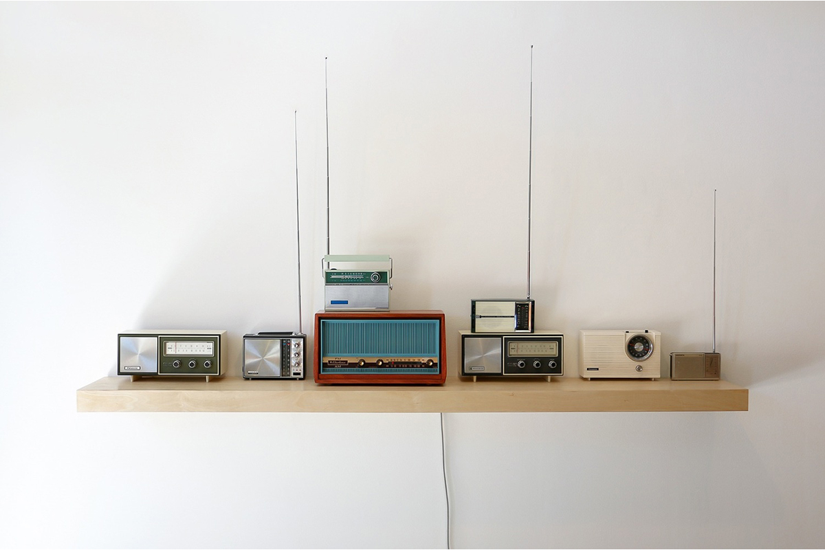 "Jimena Sarno, by international agreement, 2017. 8 radios, custom built shelf, archival recordings of the NATO spelling alphabet, 174 Hz and 639 Hz frequencies, radio transmitter. 1'02"". Courtesy of the artist."