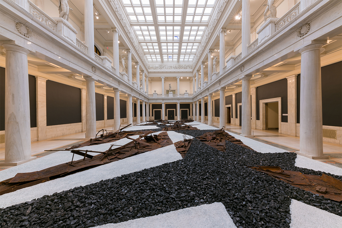 Postcommodity, From Smoke and Tangled Waters We Carried Fire Home, 2018. Sculptural graphic score for solo jazz performance. Steel, coal, glass. 3200 sq feet. Commissioned by the 57th Carnegie International. Winner of the 2018 Fine Prize. Installation views and performance, Hall of Sculpture, Carnegie Museum of Art, Pittsburgh, PA. Photos by Bryan Conley. Courtesy of the 57th Ed. Carnegie International.