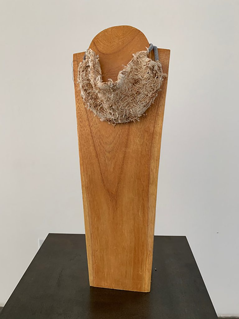 """Melinda Smith Altshuler, COVID Couture in a time of unrest, 2020. Hand knit of strings of teabags, Tee shirt scrap, on wooden display. 24"""" x 8"""" x 5"""". Installed and shot at the artists studio. Courtesy of the artist."""