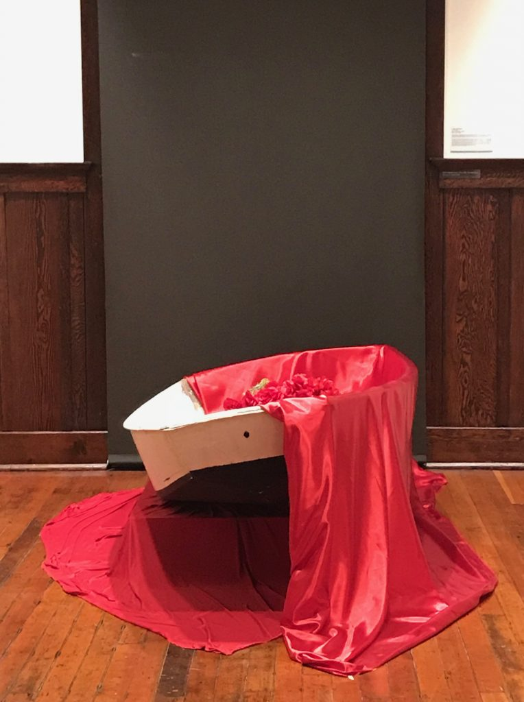 Luigia Gio Martelloni, Sea of Promises, 2018. Wooden boat, red fabric, artificial roses and mix media archival inkjet print. Courtesy of the artist.
