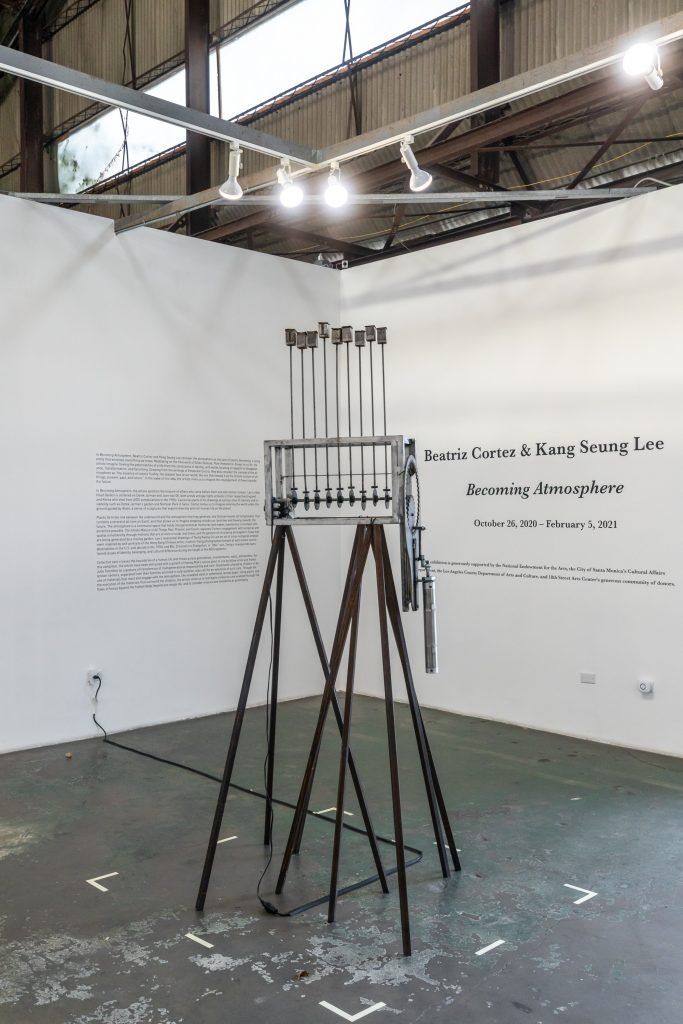 Beatriz Cortez, The Infinite Mixture of All Things Past, Present, and Future, 2019. Steel, motor, piston, paper, soil, plants indigenous to the Americas, Approx. 48 x 24 x 12 inches (122 x 61 x 30.5 cm.). Installation view at 18th Street Arts Center. Photo by Marc Walker.
