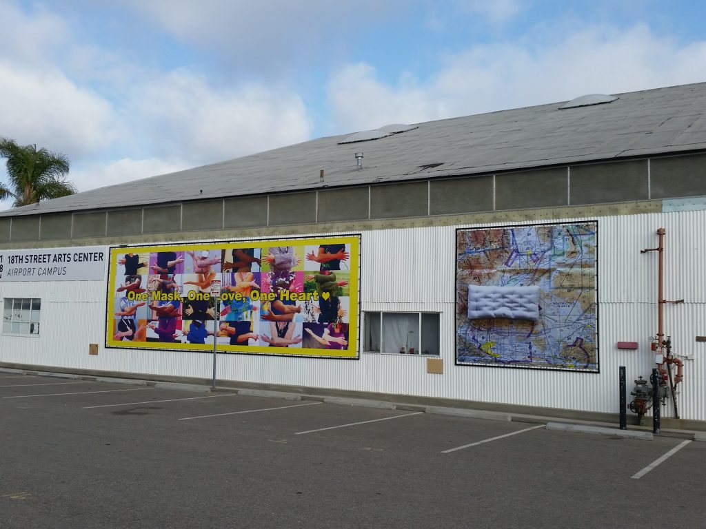 """Installation view of """"Recovery Justice: Being Well"""" vinyl murals by Lola del Fresno, Susie McKay Krieser and Yrneh Gabon, and Luciana Abait, on the Glider Wall at 18th Street Arts Center, Santa Monica Airport."""