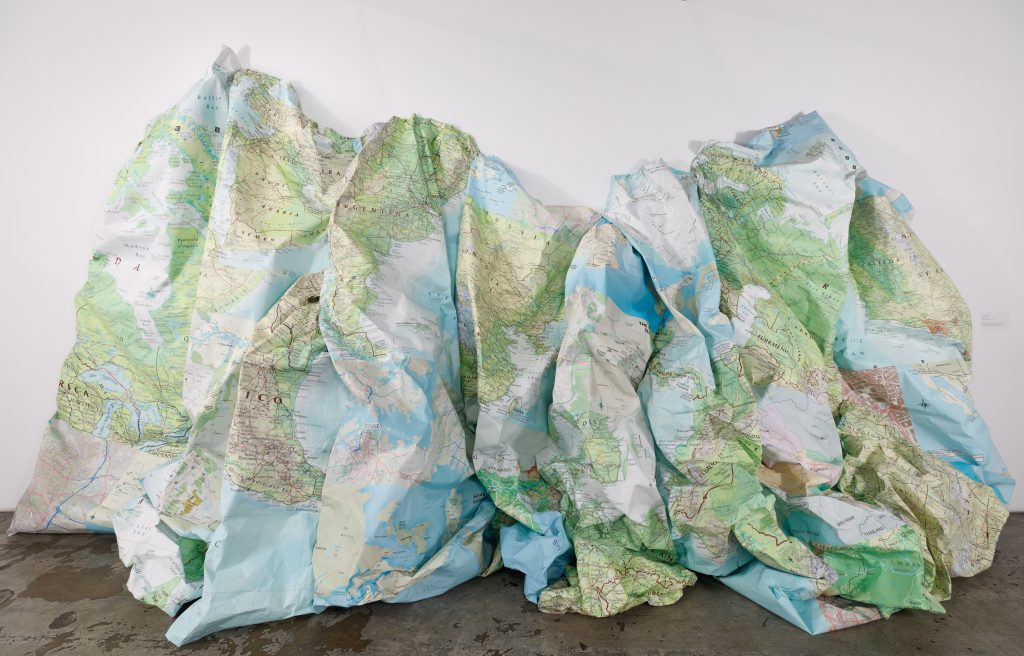 Luciana Abait, The maps that failed us, 2018 – 2021. Maps of the world and cardboard boxes. Courtesy of the artist. Photo by Marc Walker. The maps that failed us depicts a map of the world, enlarged and reconfigured. The adaptation allows one to view the imagery of geography and nature from a new perspective. It is intended to encourage conversation surrounding the complex relationship between humans and the natural environment by emphasizing countries that are affected by climate change and natural disasters.