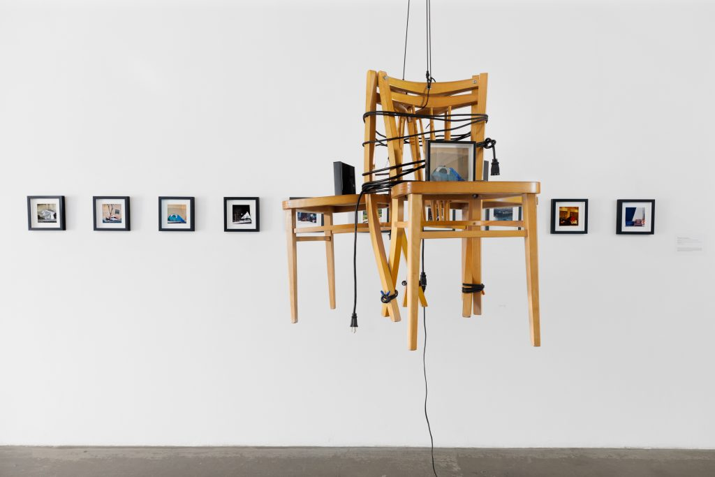 Melinda Smith Altshuler, Ascension, Suspension to Cultural Blindness/Correcting Vision, 2020 – 2021. Framed color inkjet prints, bound wood chairs, black twine, electric cords, antique hook. Courtesy of the artist. Photo by Marc Walker. Ascension, Suspension to Cultural Blindness/Correcting Vision highlights how words and intentions can be altered despite those who may be dependent upon them. These small-scale photographs depict the tents of shelters in Los Angeles, while juxtaposing larger images of bathrooms, a human necessity. Suspended and tied together, chairs symbolize the unstable condition of being unhoused.