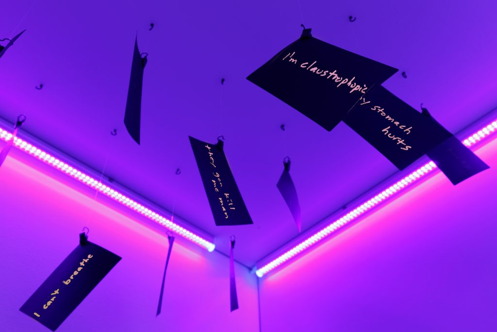 Lionel Popkin, Room to Look Up? George Floyd 8:46, 2021. Index cards, hooks, fishing line, wood, fabric and black light. Courtesy of the artist. Photo by Marc Walker. Raised in Indiana to an Indian mother and a Jewish father, Popkin's identity has inspired his work as it has placed him in a position to question racial and social issues and the injustices that have occurred in American history. In the installation Room to Look Up? George Floyd 8:46 the viewer must first bow their head, as if an act of contrition, in order to enter the space. Once inside, a release of conformed tension is achieved by raising one's head up in order to read the note cards overhead.